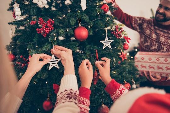closeup of kids decorating a christmas tree