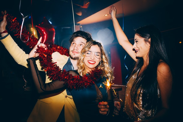A group of friends dances in a club on New Year's Eve.