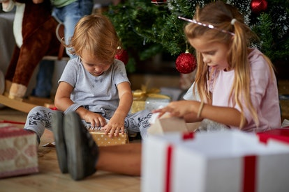 Merry Christmas and Happy Holidays! Cheerful cute childrens  opening gifts.