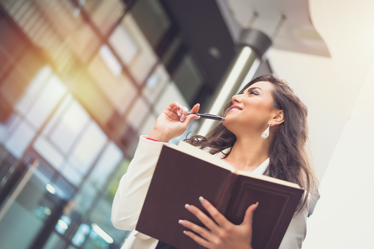 Smiling business woman standing in front of corporate building taking notes