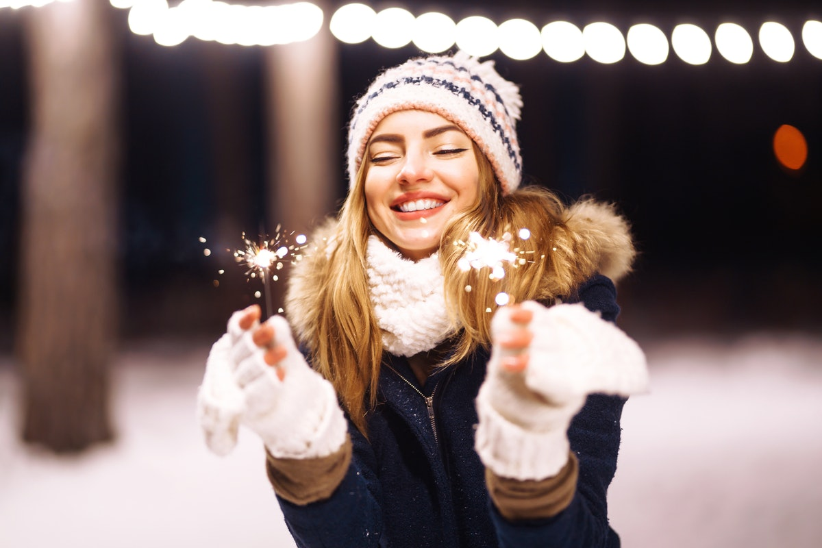Cheerful young woman holding a sparkler in hand  in the winter forest. Happy cute girl in knitted ha...