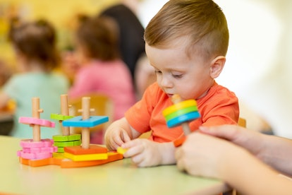 Adorable cute baby boy plays with educational sorter toys at kindergarten or nursery. Healthy happy toddler kid learning sorting colors and forms