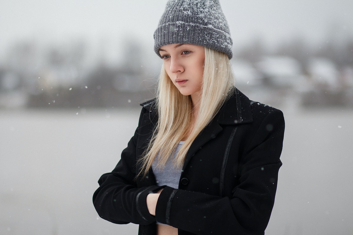 Girl winter on stroll. Girl at the frozen river. Girl in a black cloak in the snow. White snow falls...