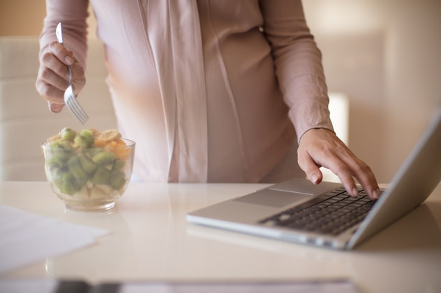 Take a break for a healthy snack. Pregnant woman eating fruit salad. Close up.