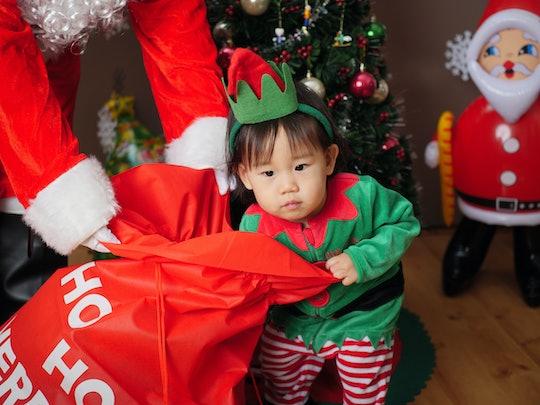 toddler pulling Christmas gift out of santa's bag