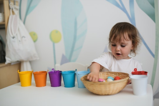charming toddler girl sorts colorful toys by colored buckets at the table
