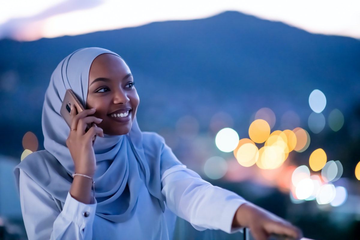 Young modern Muslim woman wearing scarf veil on urban city  street at night texting on smartphone wi...