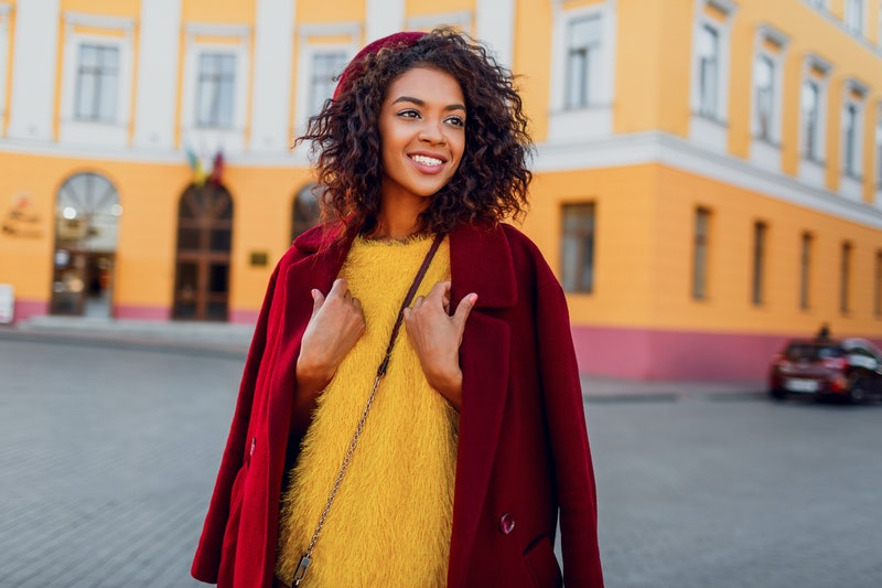 Fashionable black girl in amazing winter outfit and accessories posing on yellow background. Wavy ha...