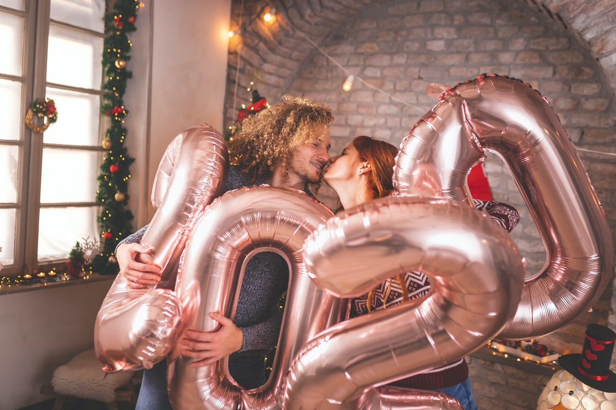 Beautiful young couple in love celebrating New Year, kissing and holding giant balloons shaped as nu...