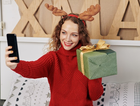 Pretty smiling young woman in reindeer antlers taking selfie with Christmas present