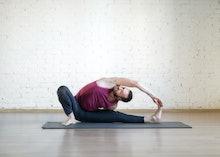 Caucasian man doing yoga, stretching on grey mat in fitness studio