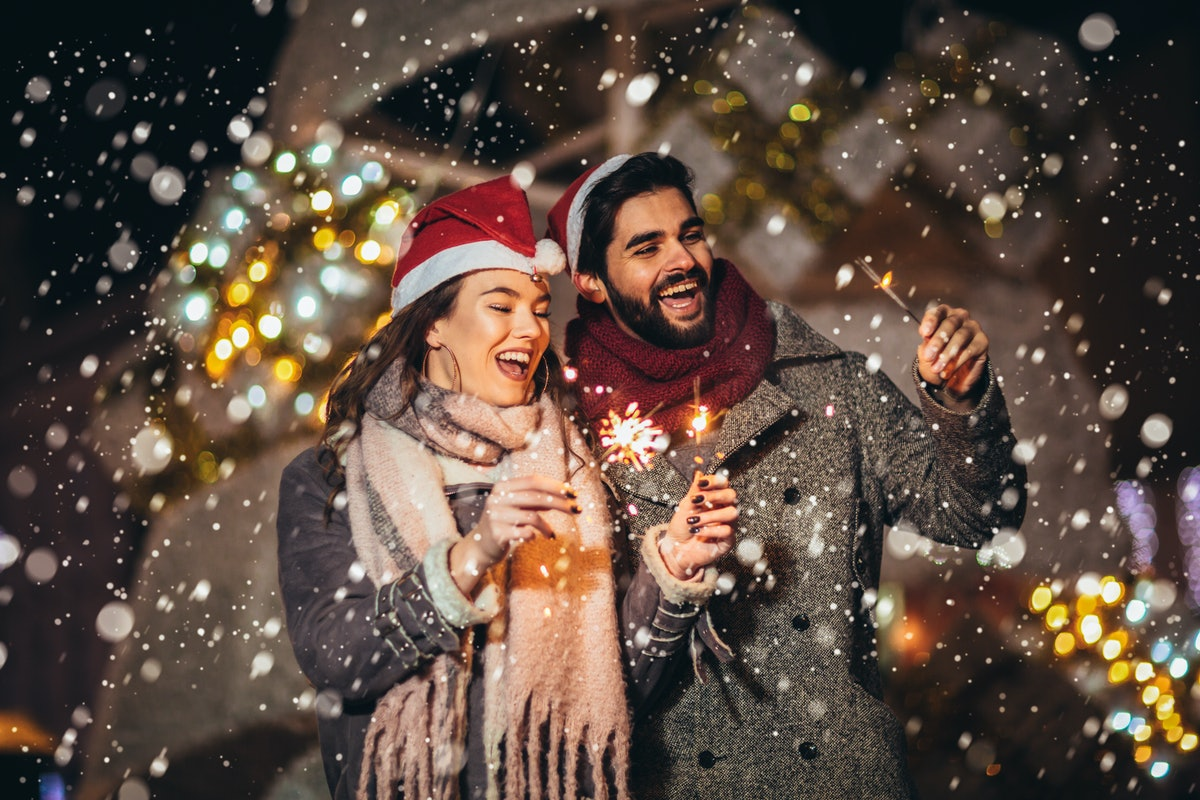 Young loving couple burning sparklers by holiday illumination on New Years eve.