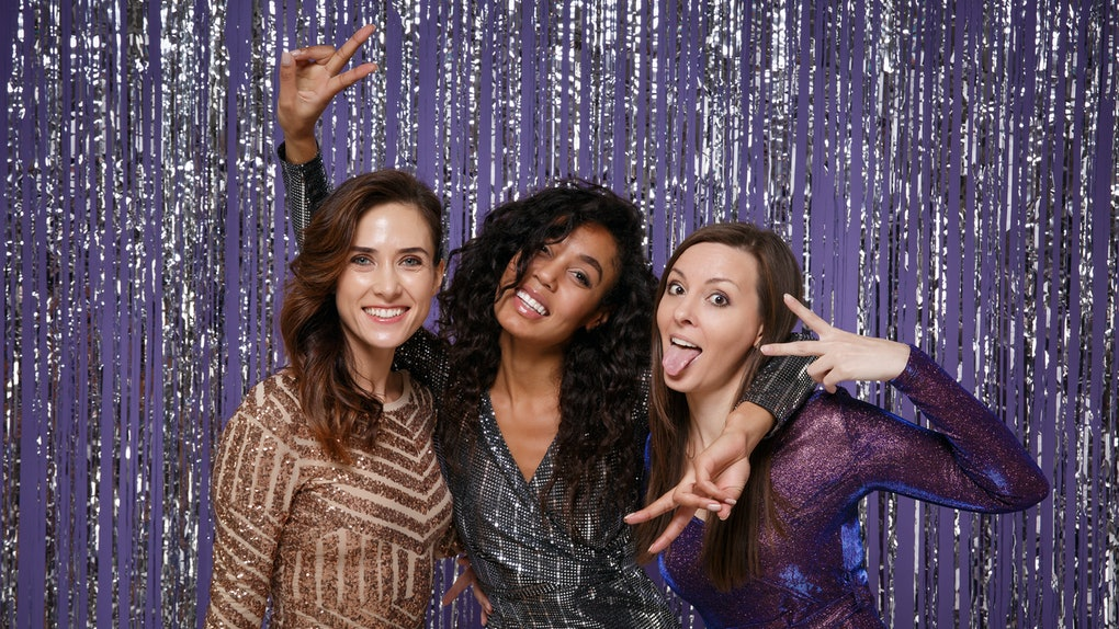 Beautiful cheerful women in fancy sparkling dresses posing isolated over vibrant purple violet silver background. Positive people spending time on happy birthday new year holiday party discotheque