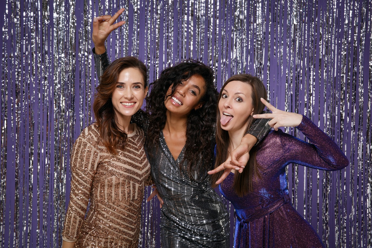 Beautiful cheerful women in fancy sparkling dresses posing isolated over vibrant purple violet silve...
