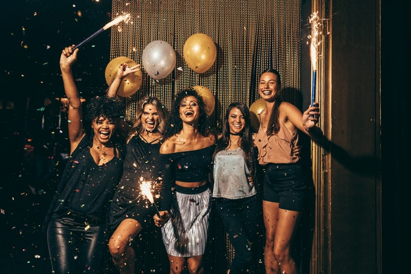 Shot best friends celebrating new year's eve holding sparklers in a party. Group of women having party at nightclub.