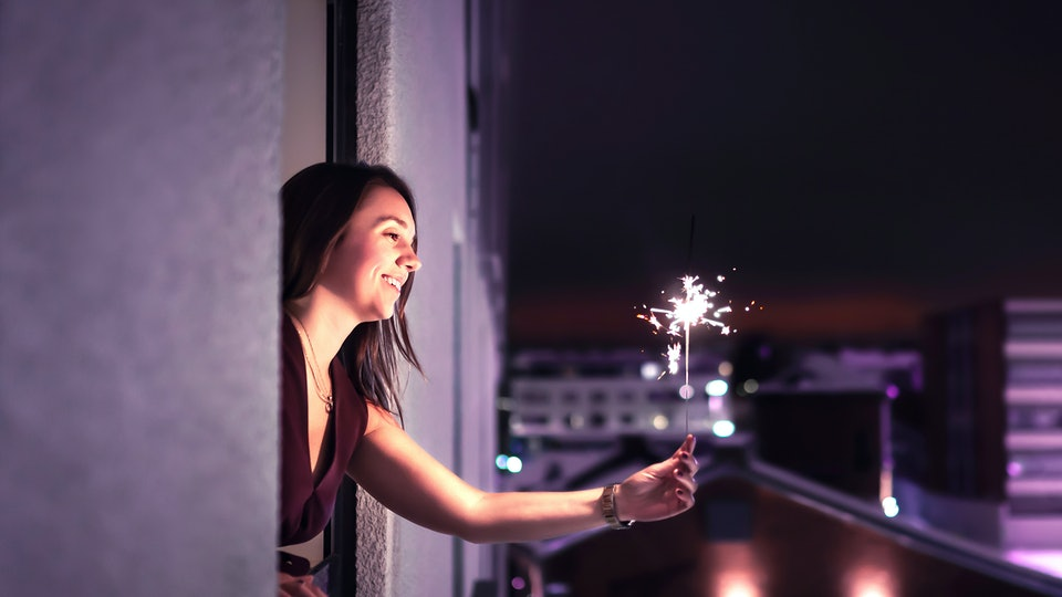 Woman holding a sparkler out of window on new year's eve 2020