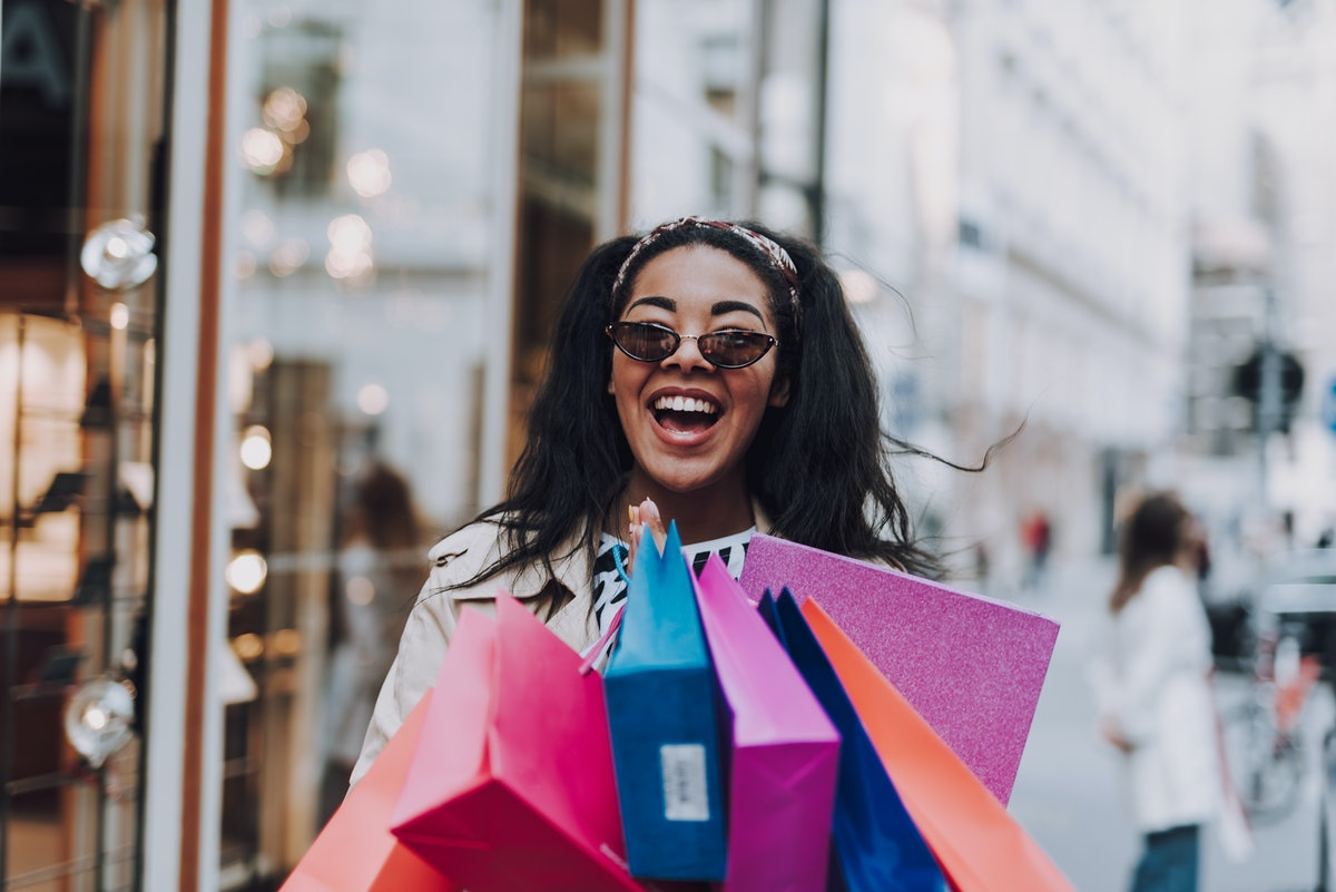 A smiling woman in sunglasses holds a bunch of colorful shopping bags on a sunny day.
