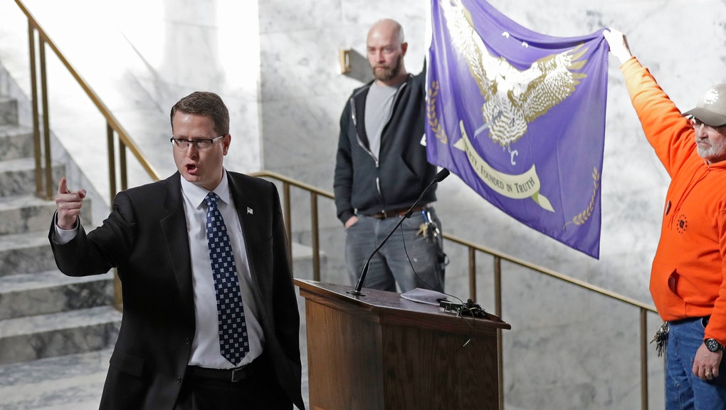 Rep. Matt Shea, left, R-Spokane Valley, gestures as he gives a speech in front of the liberty state flag, at the Capitol in Olympia, Wash., during a rally held by people advocating splitting Washington state into two separate states and questioning the legality of Washington's I-1639 gun-control measure. Shea is one of the sponsors of House Bill 1509, which would split Washington state in half along the Cascades, separating Eastern Washington from Western Washington