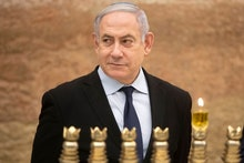 Israeli Prime Minister Benjamin Netanyahu looks on after lighting a Hanukkah candle at the Western W...