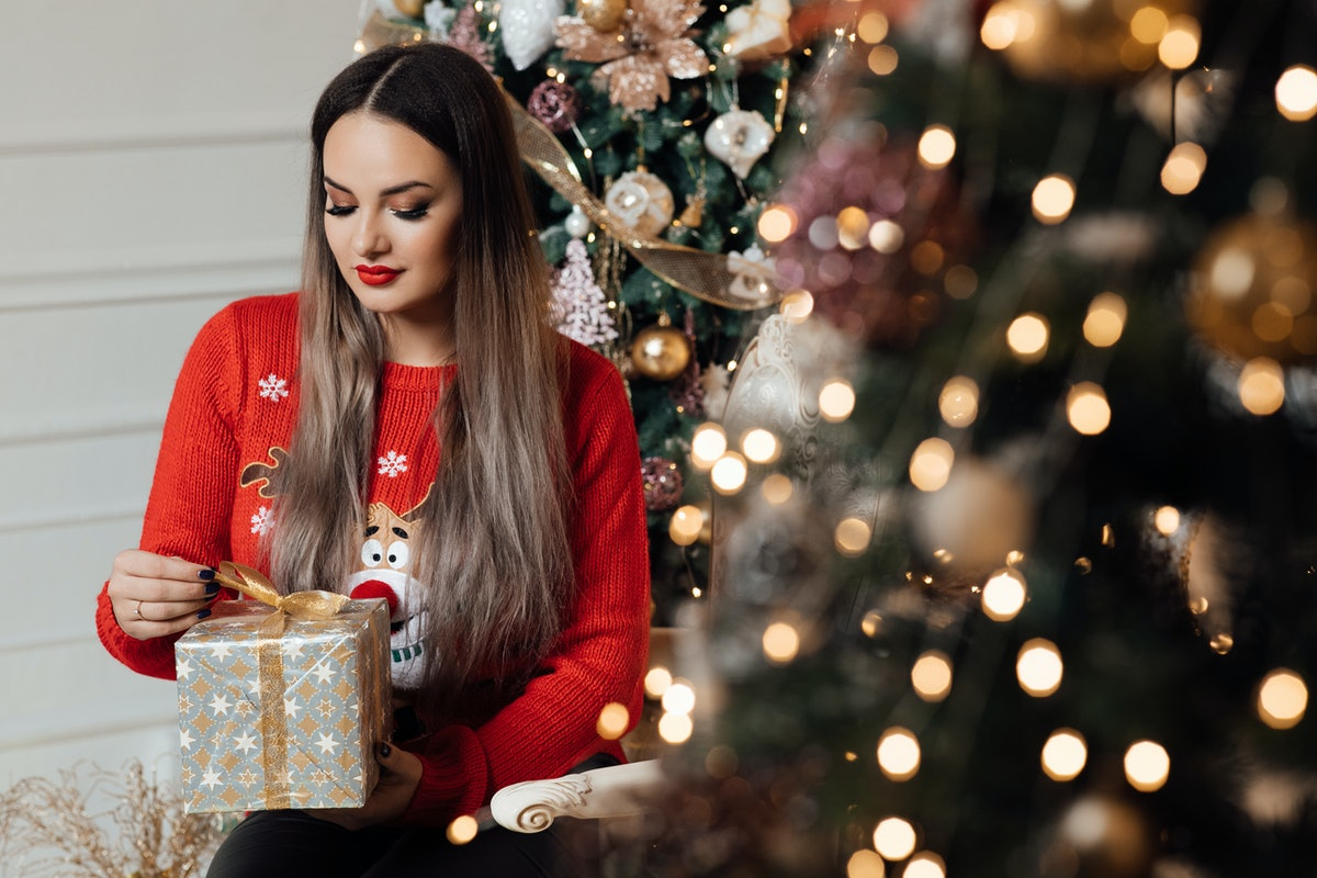 The girl holds gift box in her hands. Happy new year. Christmas. Beautiful smiling woman. Makeup. El...
