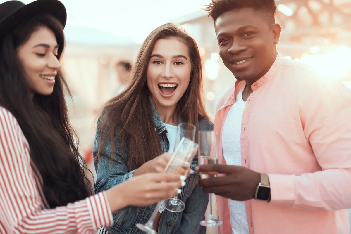A group of three friends smile and toast their champagne flutes outside on a sunny day.