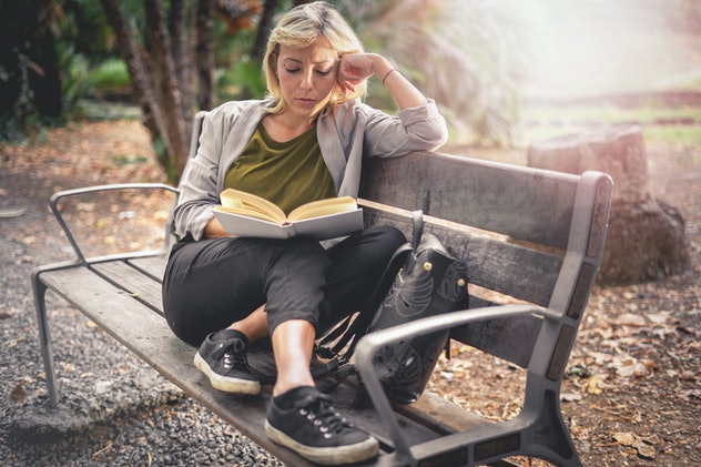 Blonde young adult woman reading on a public garden sitting on a park bench. Students learning studying outdoors concept.