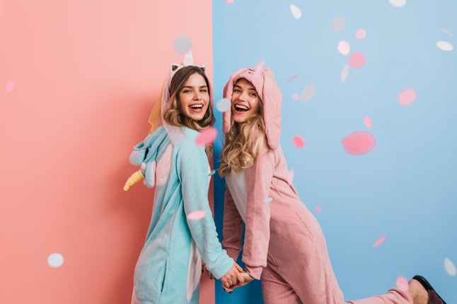 Dreamy girl in rabbit kigurumi holding hands with friend. Ecstatic ladies in cute pajamas dancing and smiling.