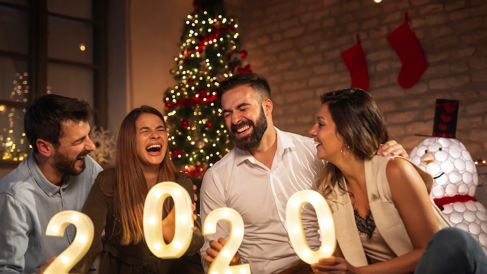 Group of young friends having fun at New Years party, holding illuminative numbers 2020 representing the upcoming New Year at midnight countdown