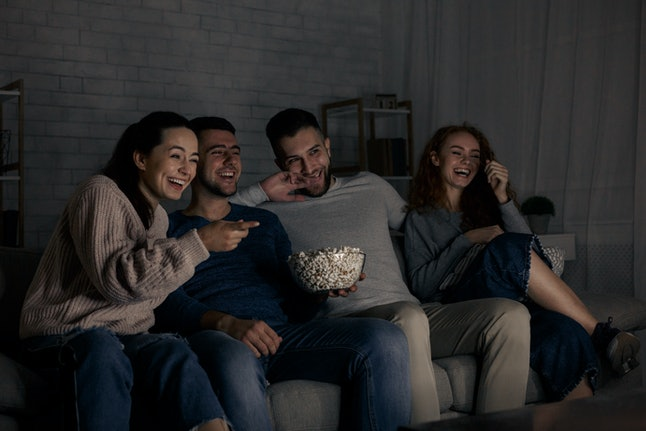 Happy friends watching comedy film and laughing, relaxing at home together