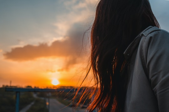 Anonymous woman looking to sunrise