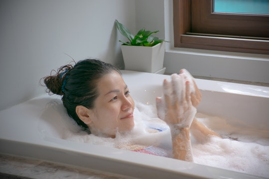 young asian woman relaxing in the bath tub