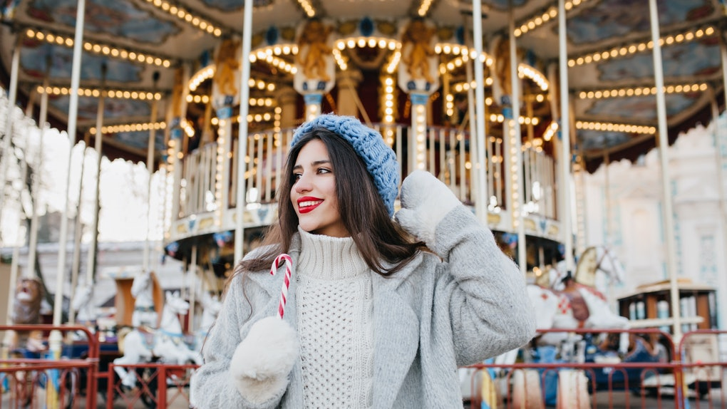 A stylish woman in a grey jacket and blue knitted hat holds a candy cane and poses in front of a carousel during a winter festival.