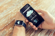 technology, application, weather forecast and people concept - close up of male hand holding smart p...
