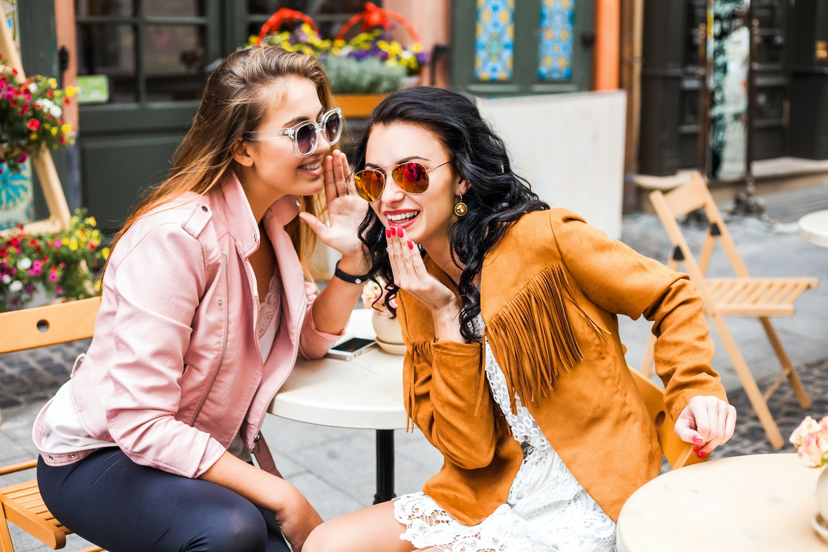 Two best friends whisper secrets to each other while sitting at an outdoor cafe.