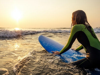 woman in a diving suit lying on a surfboard waiting for a big wave