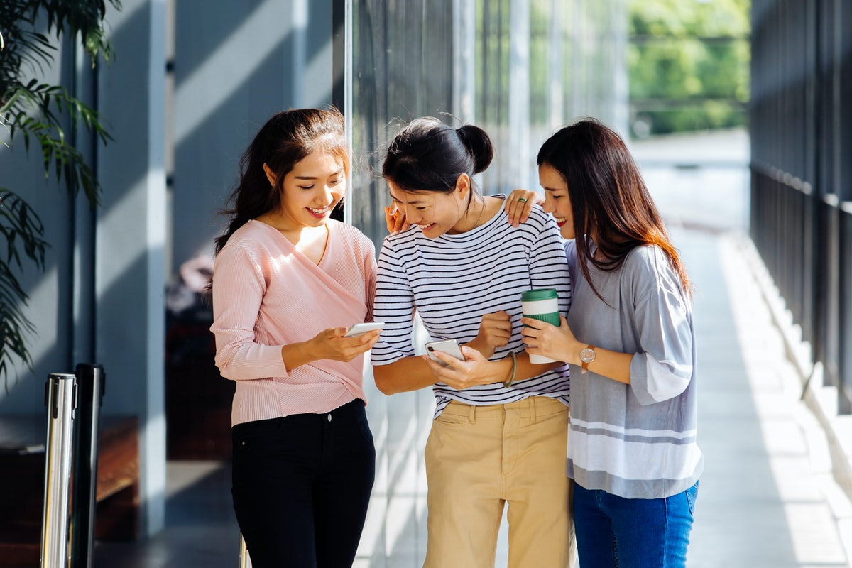 Three female coworkers smile and laugh outside on a sunny day while looking at a cellphone.