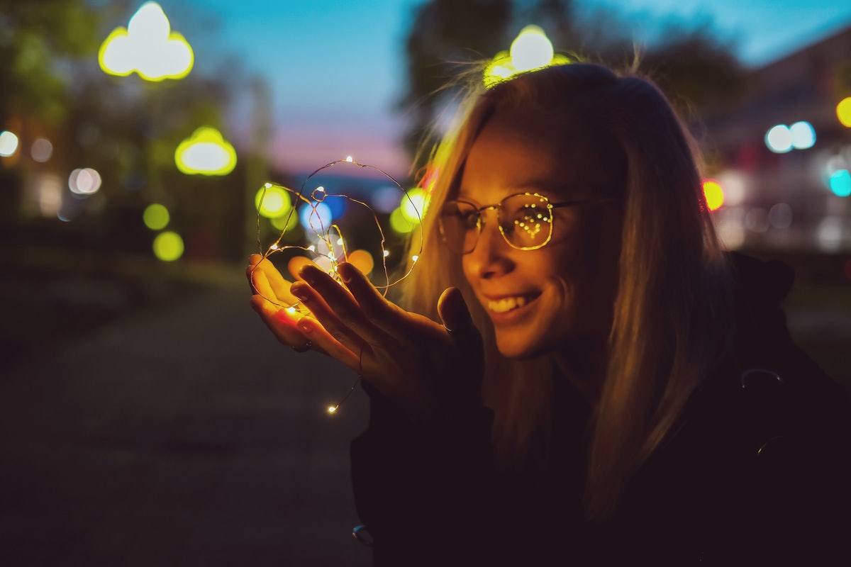 Romantic portrait of a girl with lights on the night street