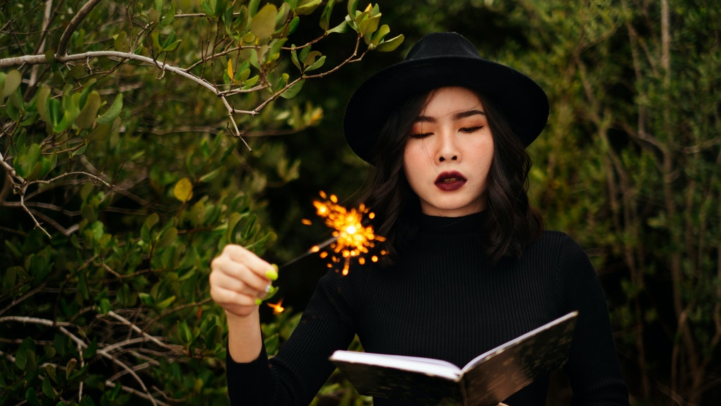 Black witch try to make a spell with her wand and magic book.