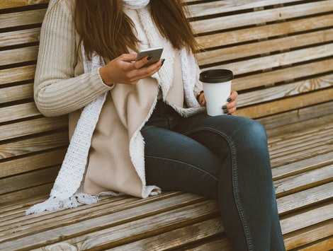 Unrecognizable beautiful young girl drinking coffee, tea from a plastic mug in autumn, winter and talking on mobile phone. Woman with long hair sitting on bench in autumn or winter