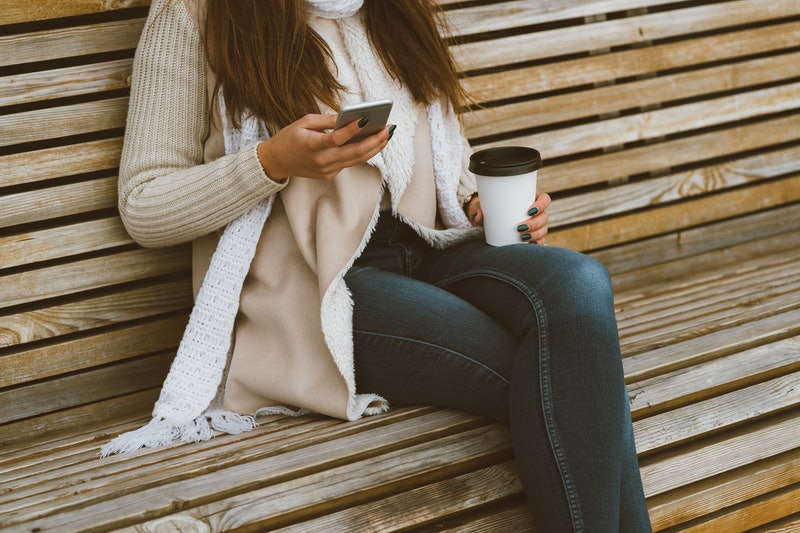 Unrecognizable beautiful young girl drinking coffee, tea from a plastic mug in autumn, winter and ta...