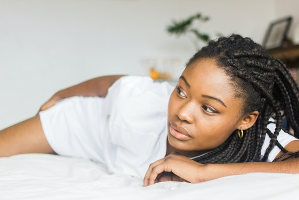 Sexy, Young African Female Model In An Oversized White T-Shirt Lying Down On A White Bed Looking Away