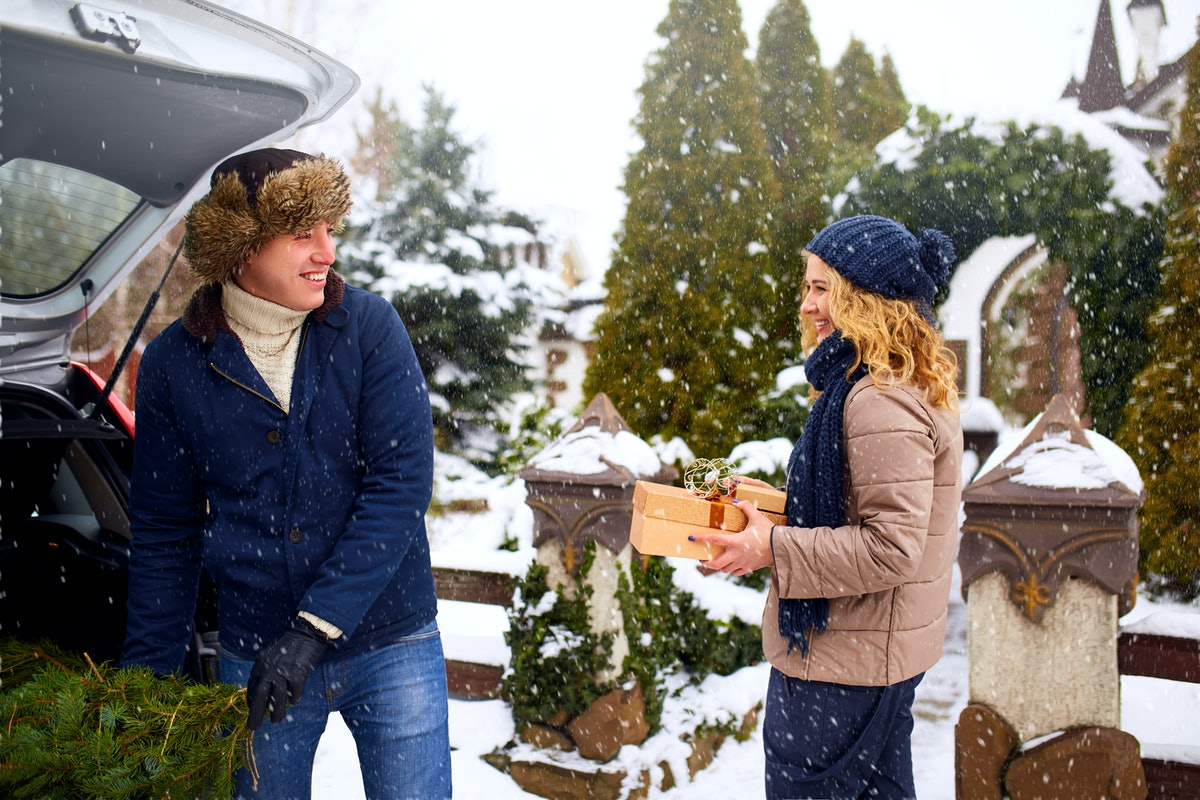 A happy couple unloads their Christmas tree from the trunk of their car while it snows outside.