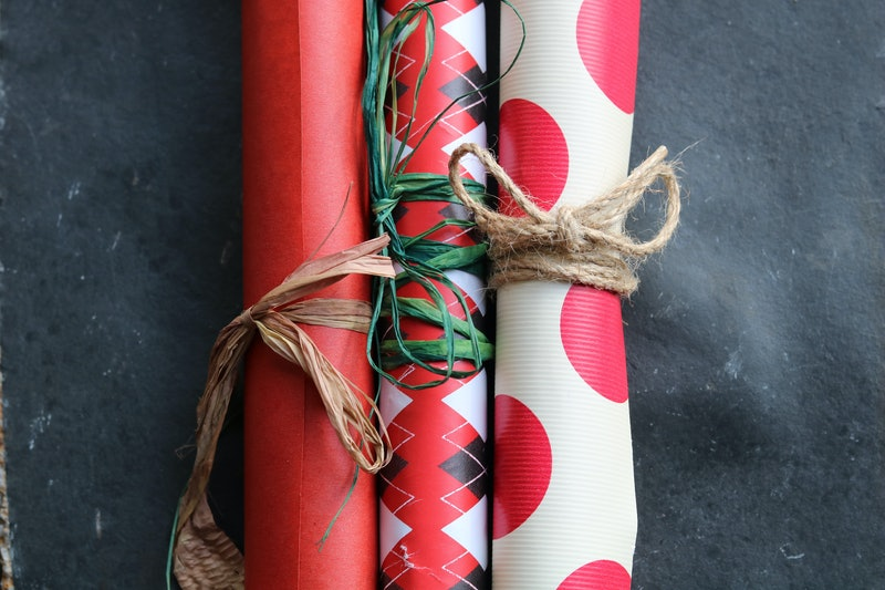 Three rolls of recycled wrapping paper on a piece of stone slate, in three different patterns; polka dot, diamond pattern, and plain matte red; tied up with left over jute and raffia.