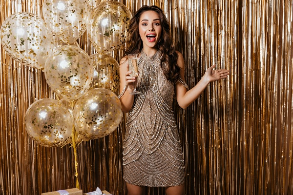 A brunette woman dressed in a sparkly beaded dress smiles and holds a glass of champagne in front of a gold backdrop on New Year's Eve.