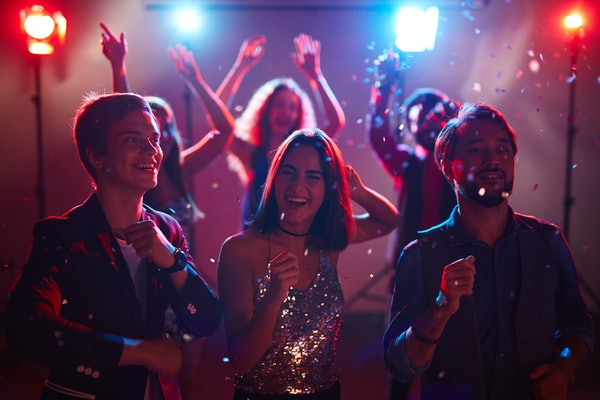 Three friends laugh and party in a dimly-lit club on New Year's Eve.