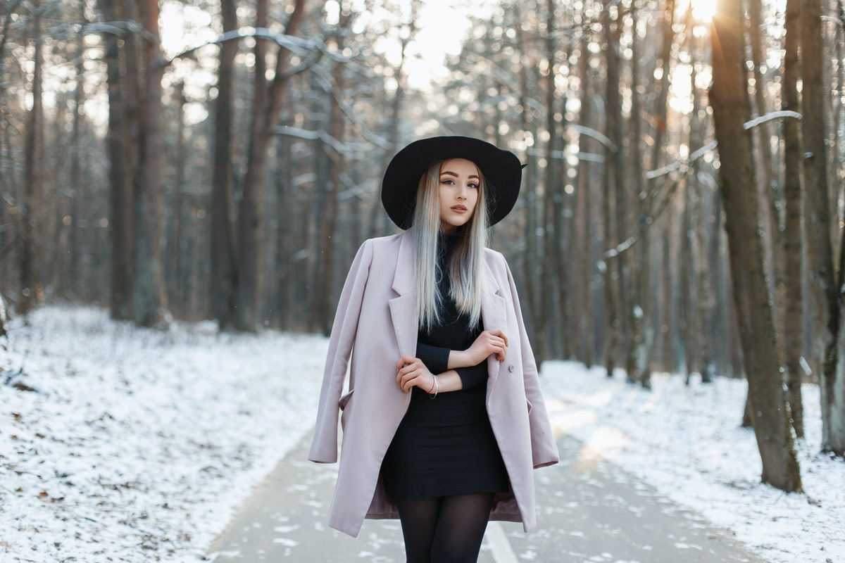 Stylish young girl walking in a winter sunny day on the background of the park with snow