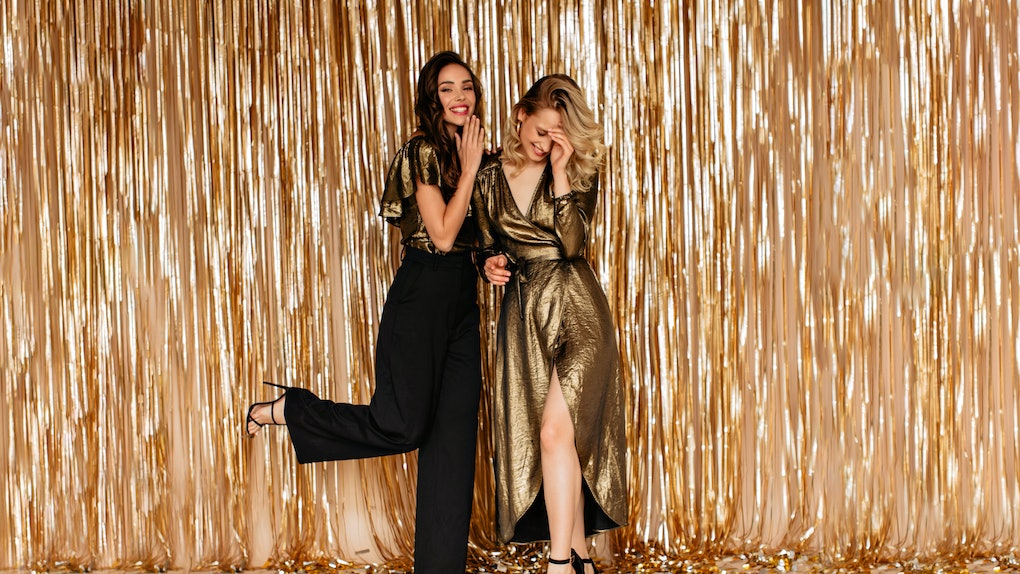 Two friends laugh in front of a gold backdrop with gold confetti on the ground at a fancy dance.