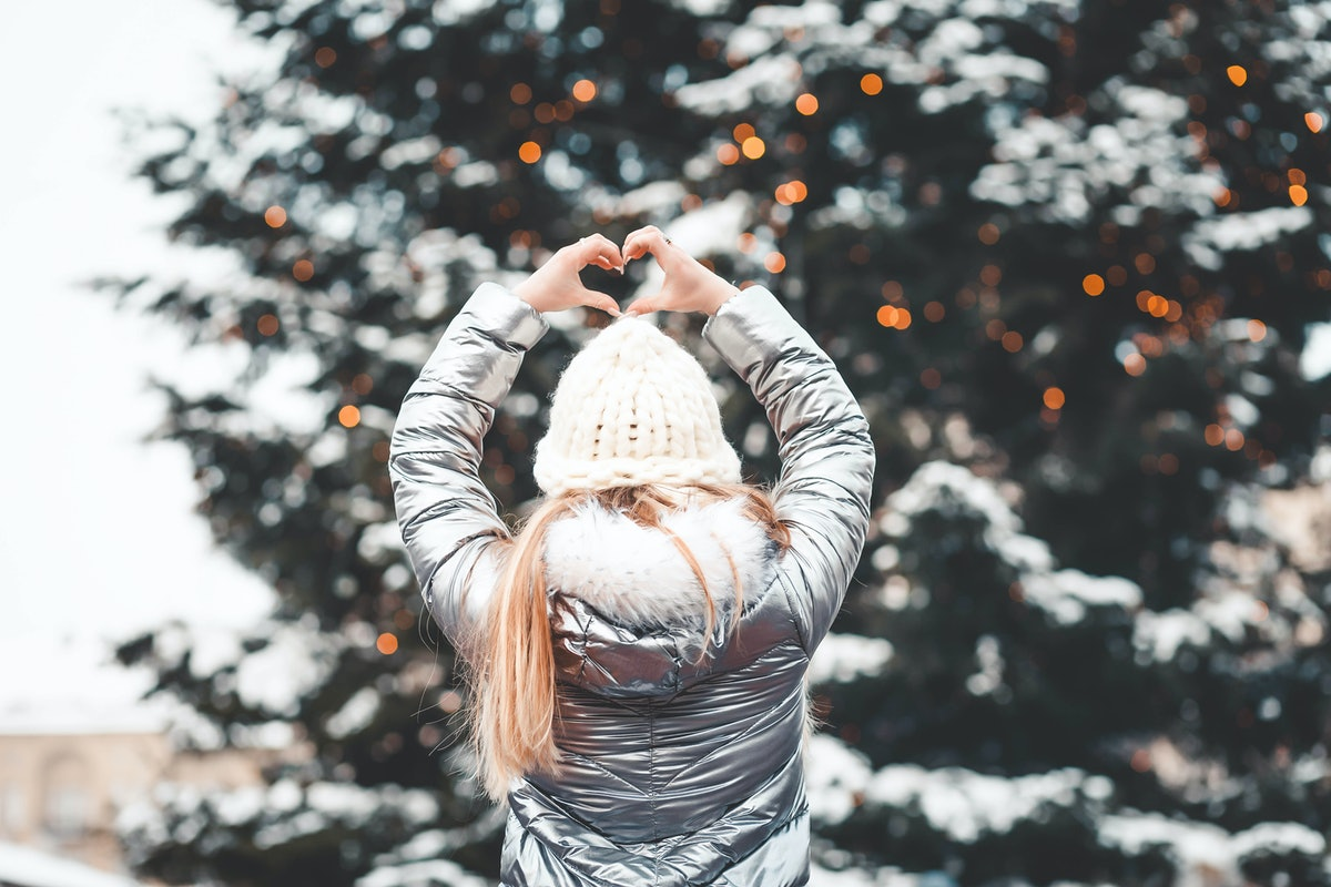 A blonde woman in a metallic jacket poses in front of a snowy, decorated Christmas tree.