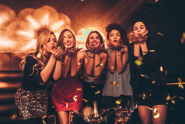 A group of women blow gold confetti into the air at a bar on New Year's Eve.