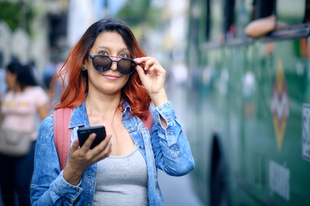 Young red hair woman with black glasses uses her cell phone in the street, green bus. Pereira, Colombia